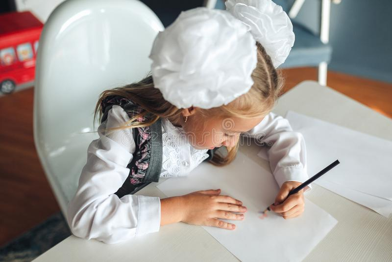 Mooi schoolmeisje die goed beeld met kleurpotloden trekken terwijl het zitten bij lijst tijdens kunstles op school meisjesschoolm stock foto's
