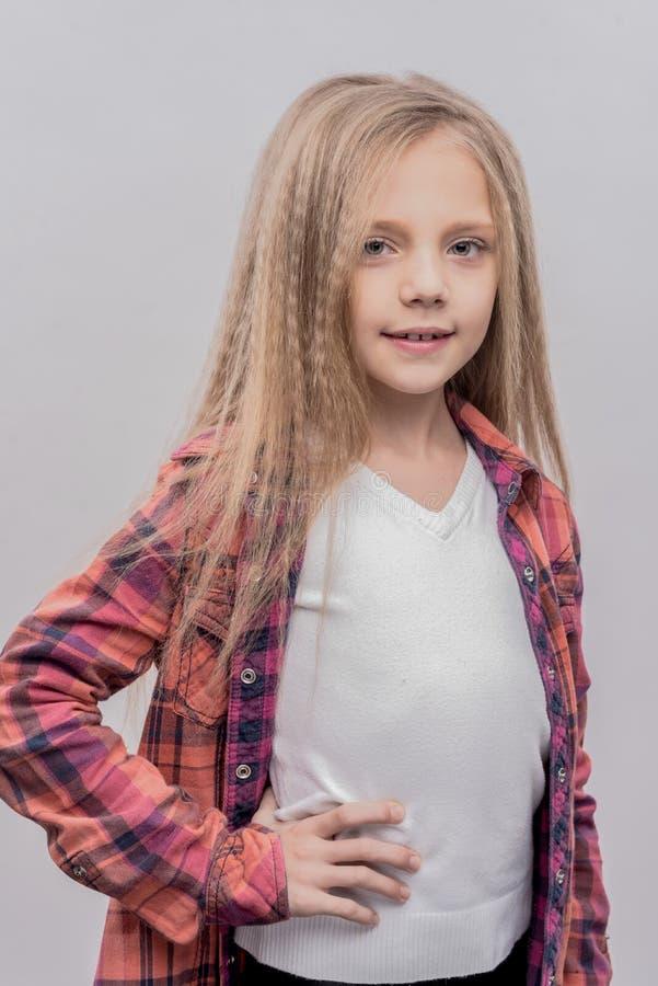 Mooi schoolmeisje die met lang blondehaar ruim glimlachen royalty-vrije stock afbeeldingen