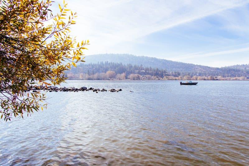 Mooi schot van een meer met een boot die op het met een zonnige hemel varen stock afbeelding