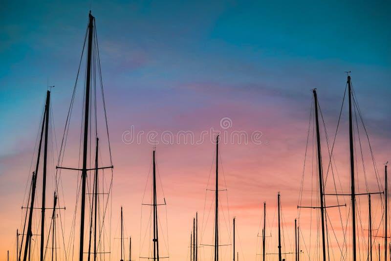 Mooi schot van een silhouet van zeilbootmasten bij zonsondergang stock foto's