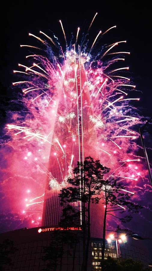 Mooi schot van roze purper vuurwerk dat uit een lang gebouw bij nacht wordt geblazen stock afbeeldingen