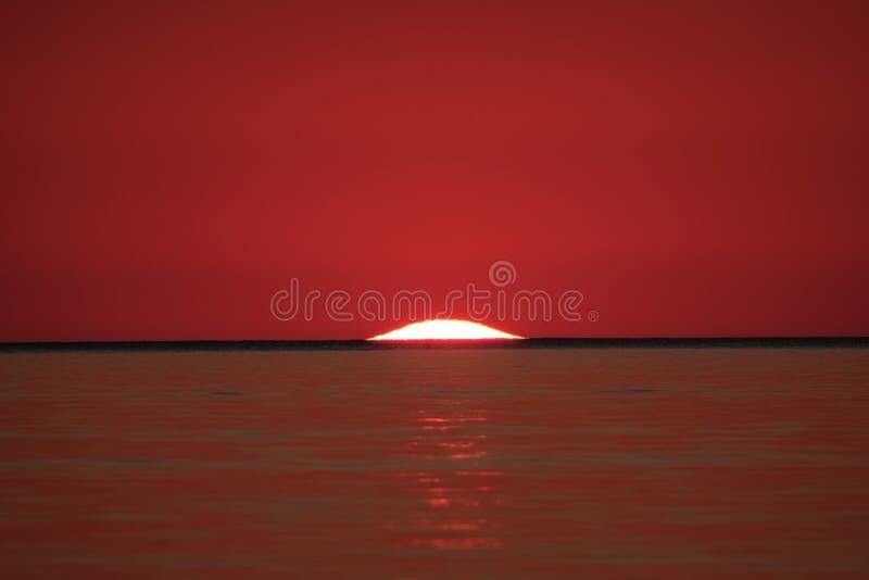 Mooi schot van zon achter het overzees die op de rode hemel wijzen bij zonsondergang royalty-vrije stock foto