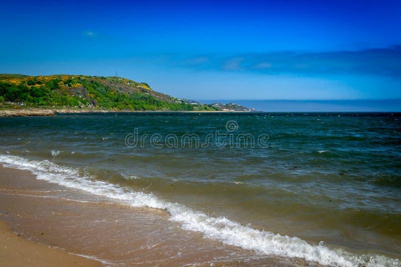 Mooi Schots strand met heldere blauwe hemel en heldergroene heuvels op achtergrond met water het bespatten in voorgrond royalty-vrije stock foto's