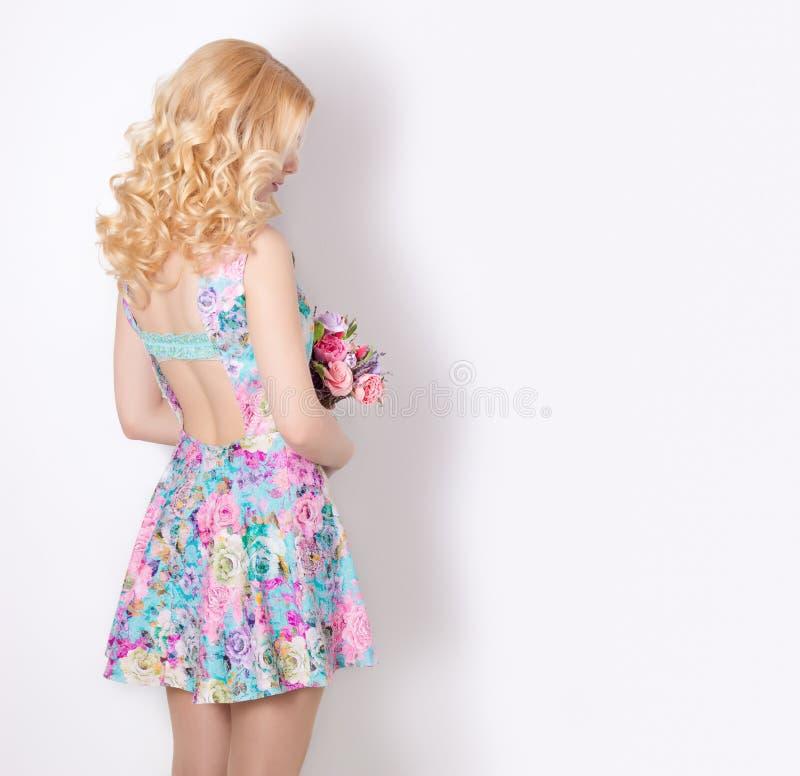Mooi sexy bescheiden zoet teder meisje met krullend blond haar die zich op witte achtergrond met een boeket van bloemen van laven stock afbeelding