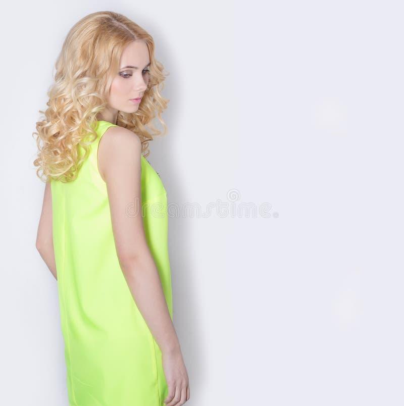 Mooi sexy blond meisje in een gele de zomerkleding met haarkrullen royalty-vrije stock afbeelding