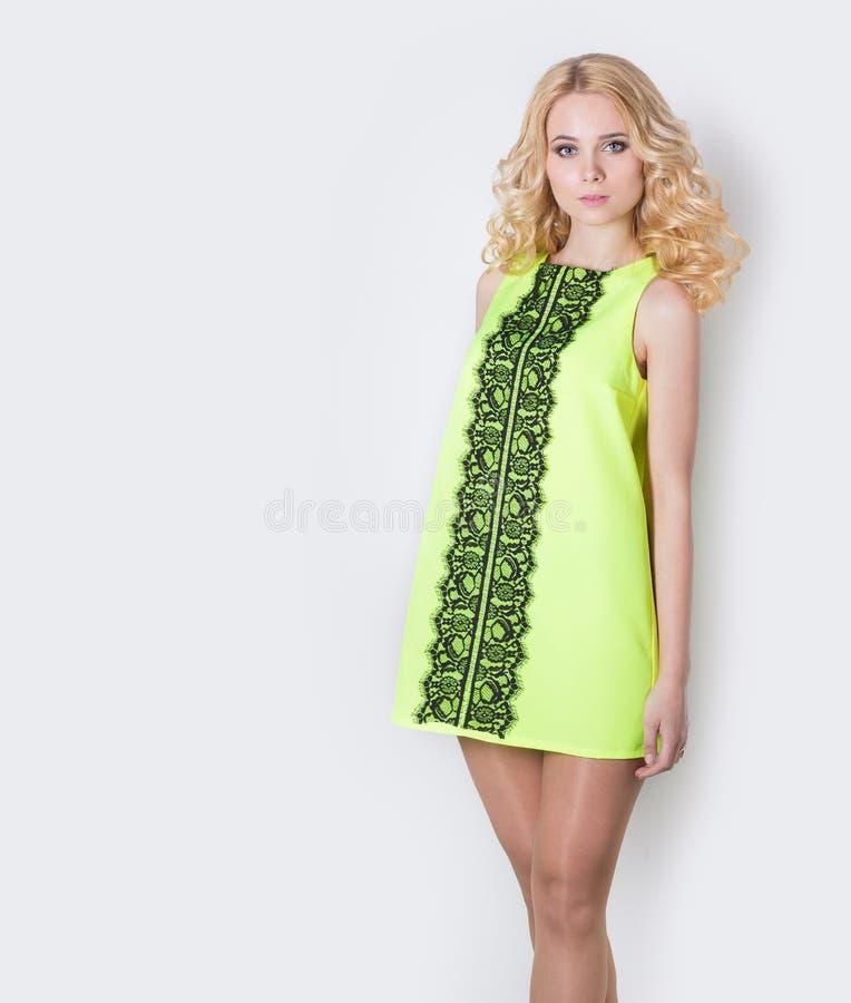 Mooi sexy blond meisje in een gele de zomerkleding met haarkrullen stock foto's