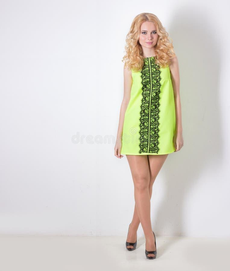 Mooi sexy blond meisje in een gele de zomerkleding met haarkrullen stock foto