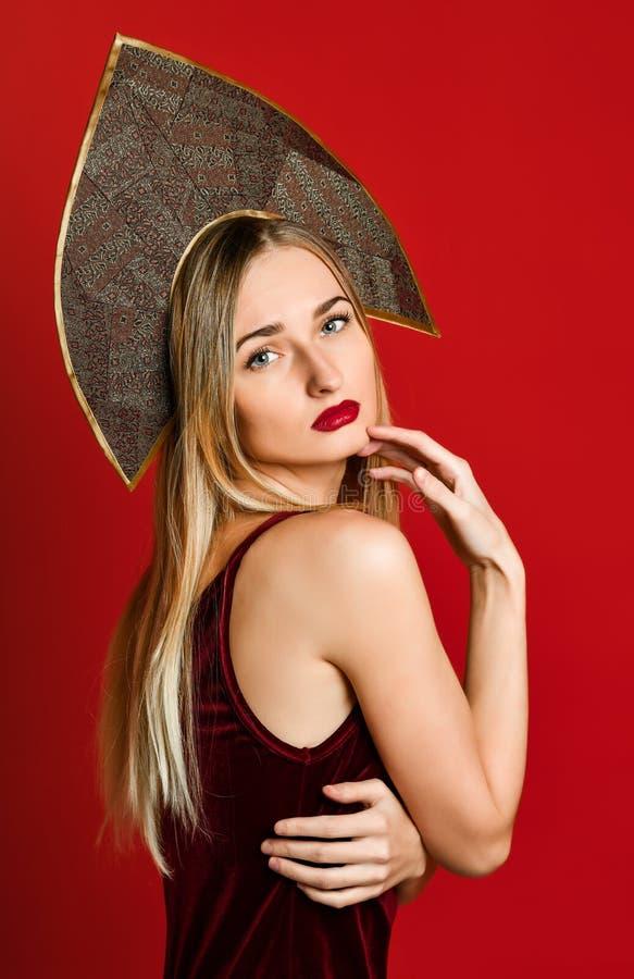 Mooi sexy blonde Russisch meisje in traditionele kokoshnikhoed, fluweel feestelijke kleding op een rode achtergrond, royalty-vrije stock foto's