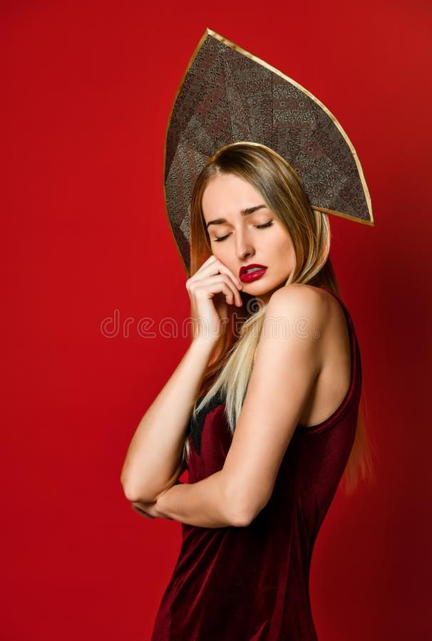 Mooi sexy blonde Russisch meisje in traditionele kokoshnikhoed, fluweel feestelijke kleding op een rode achtergrond, royalty-vrije stock afbeelding