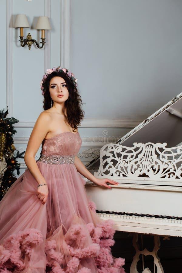 Mooi sexy brunette in wolkenkleding het stellen in een elegant binnenland van de studiopiano royalty-vrije stock fotografie