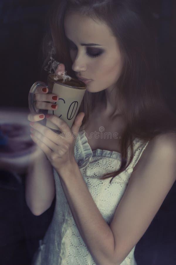 Mooi sexy donkerbruin meisje die hete aromatische koffie in het huis drinken dichtbij het venster royalty-vrije stock foto's