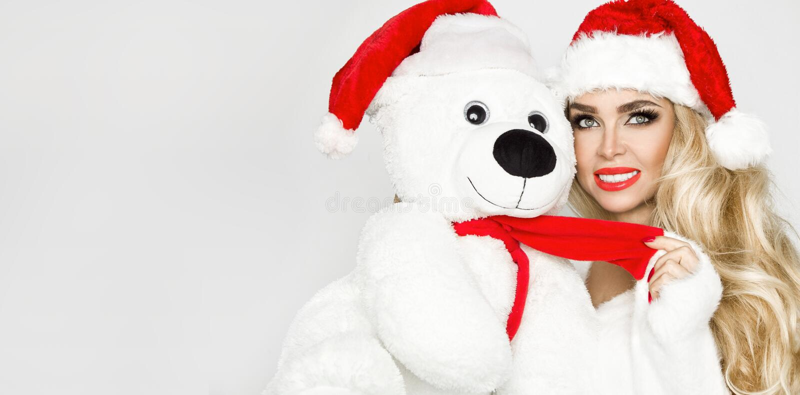Mooi sexy, het glimlachen blondemodel gekleed in een Santa Claus-hoed, die een teddybeer houden Schoonheids sensueel meisje voor  royalty-vrije stock afbeelding