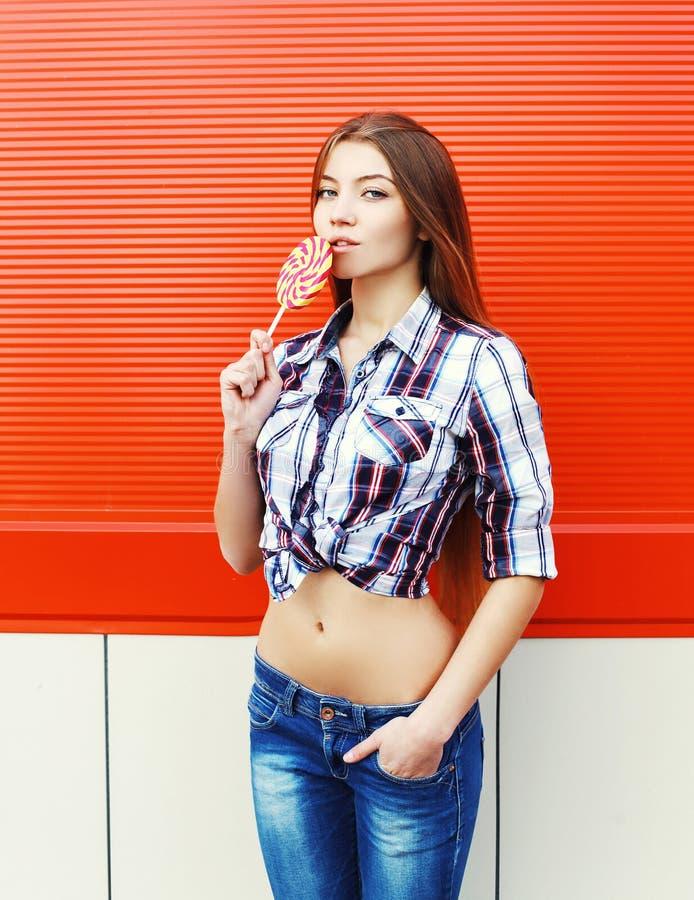 Mooi sexy jong meisje met zoete karamellolly over rood royalty-vrije stock fotografie