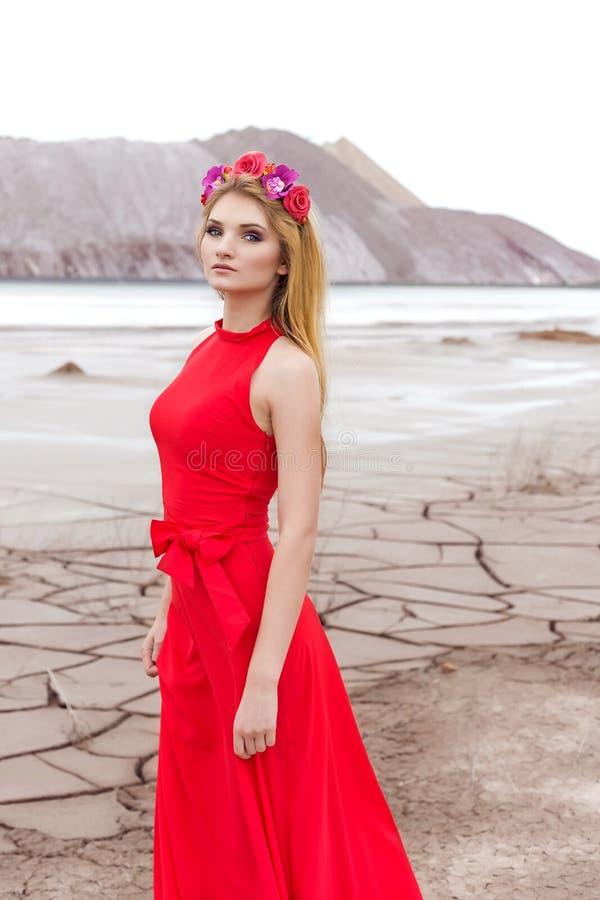 Mooi sexy leuk meisje met lang blond haar in een lange rode avondjurk met een kroon van rozen en orchideeën in haar haar status stock fotografie