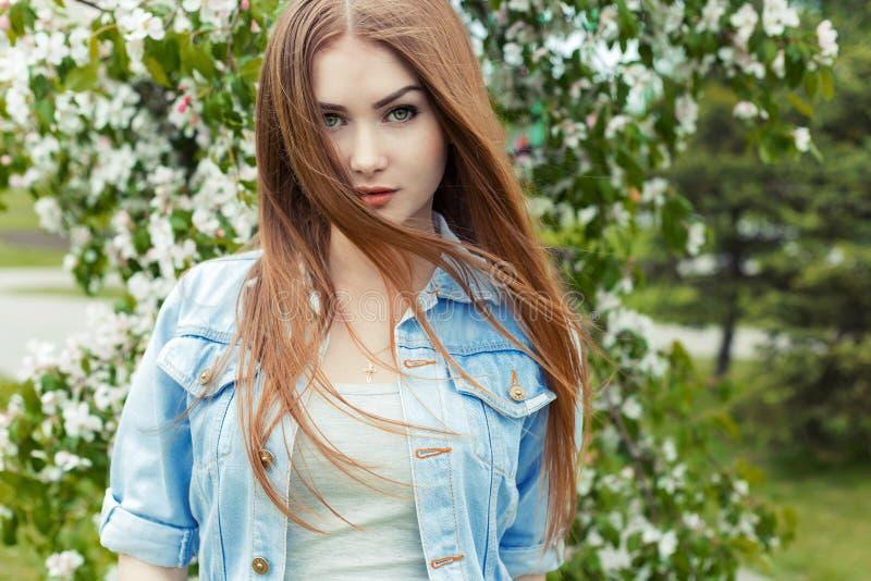 Mooi sexy leuk zoet meisje met lang rood haar en groene ogen in een denimjasje dichtbij een bloeiende boom in het park de wind stock afbeeldingen