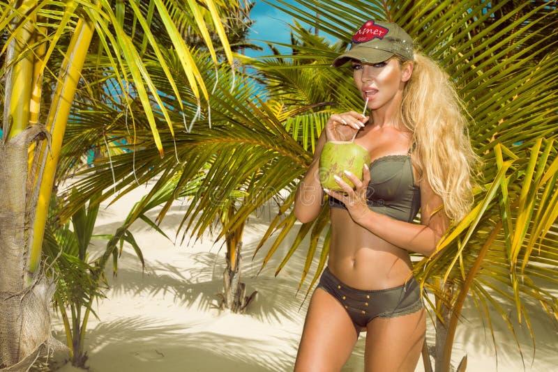 Mooi, sexy meisje in bikini die, die op het Cara?bische strand stellen en een kokosnoot houden stock foto