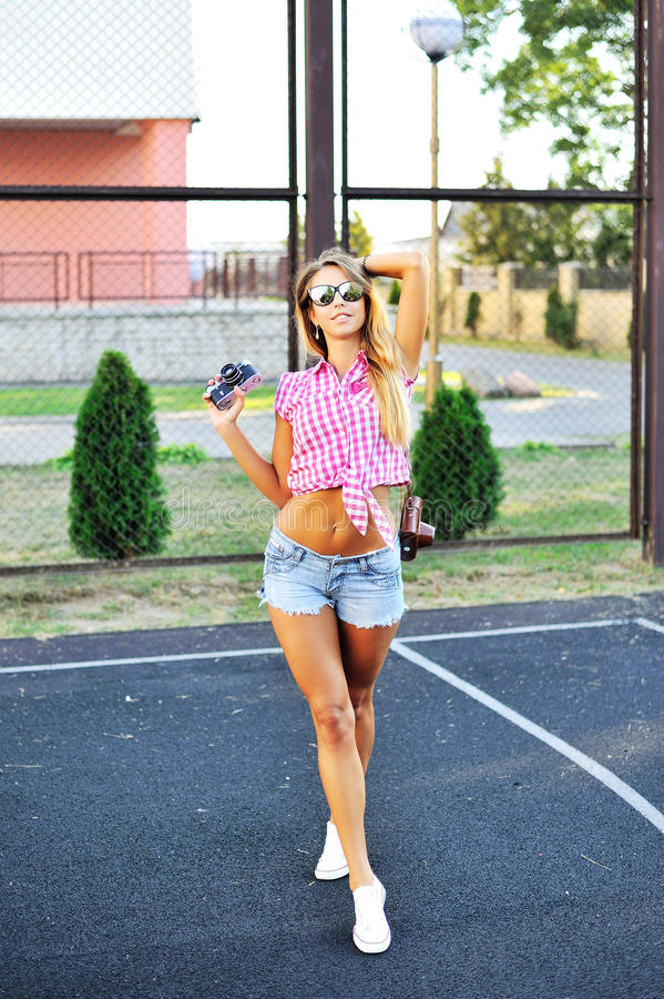 Mooi sexy meisje in borrels en zonnebril die met oude nok stellen stock fotografie