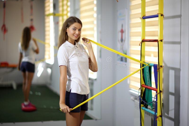 Mooi, sexy meisje in de gymnastiek Een mooi jong meisje is bezig geweest met geschiktheid met een expander stock foto