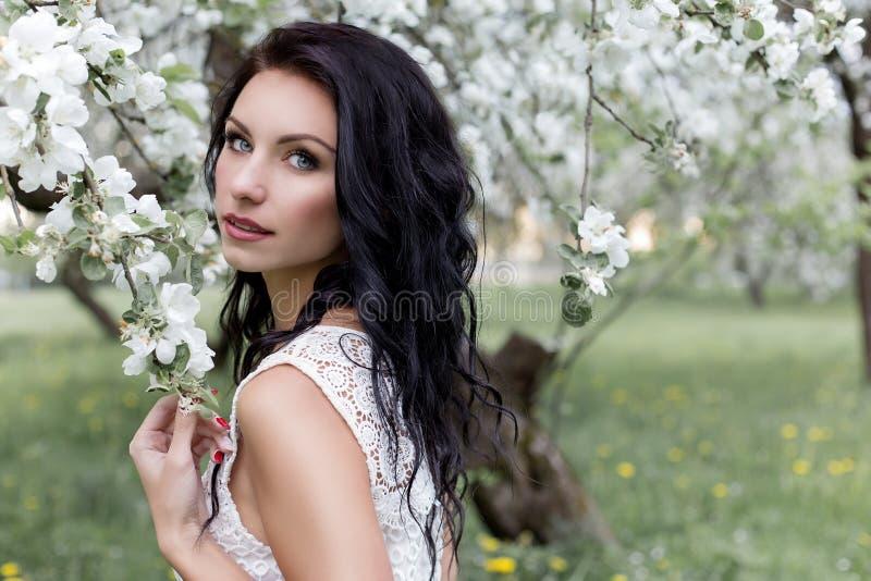 Mooi sexy meisje met lang donker haar in de witte zomer die sundress in de tuin in een tot bloei komende foto van appelbomen in m stock fotografie