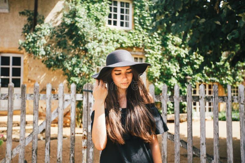 Mooi sexy meisjesbrunette met bruine ogen in een zwarte kleding en een zwarte hoed met grote randen tegen de achtergrond van een  royalty-vrije stock fotografie