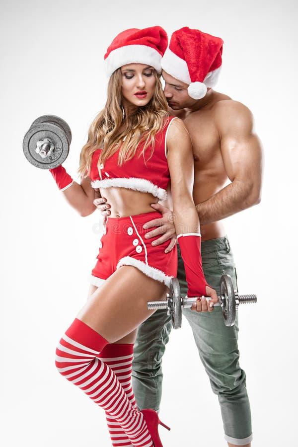 Mooi sexy paar in de kleren die van de Kerstman training doen stock afbeelding
