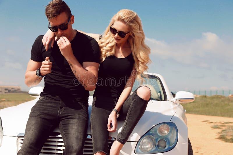 Mooi sexy paar in vrijetijdskleding die naast auto stellen royalty-vrije stock foto's