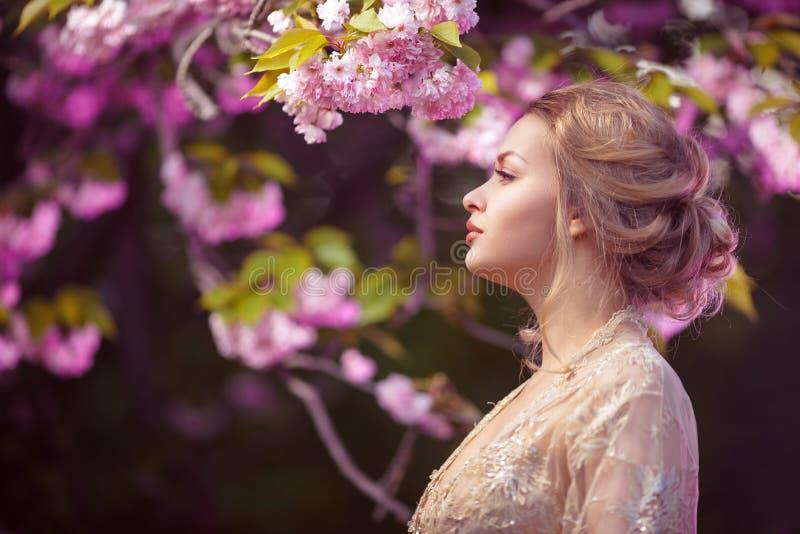 Mooi sexy volwassen meisje die zich bij tot bloei komende boom in de tuin bevinden stock foto