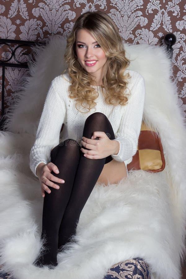 Mooi sexy vrolijk leuk meisje met een heldere glimlach sneeuwwitte zitting in een warme sweater en sokken in bed royalty-vrije stock afbeeldingen