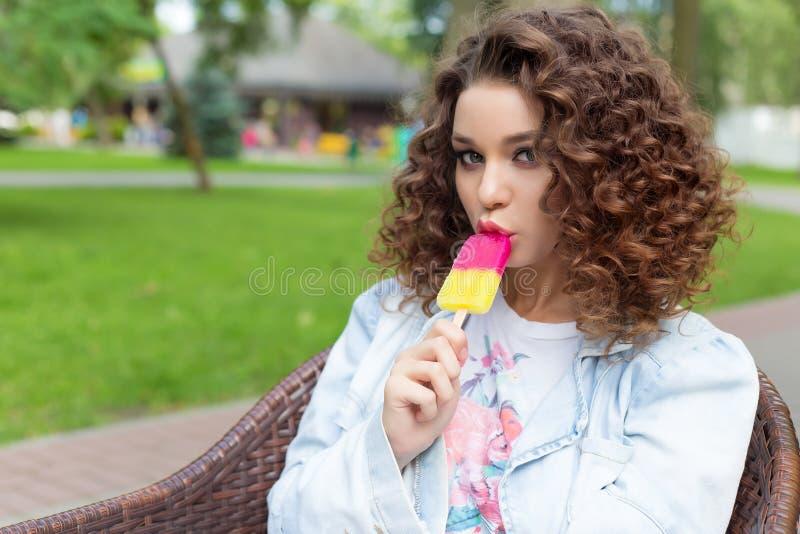Mooi sexy vrolijk meisje die met krullend haar met volledige lippen heldere kleur roomijs in het park in een de zomerkoffie eten royalty-vrije stock foto