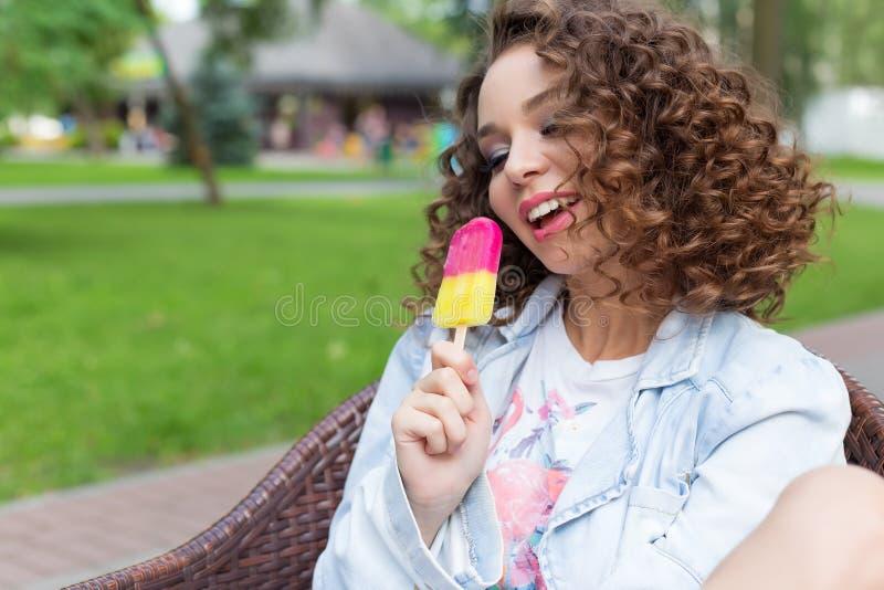 Mooi sexy vrolijk meisje die met krullend haar met volledige lippen heldere kleur roomijs in het park in een de zomerkoffie eten stock foto's