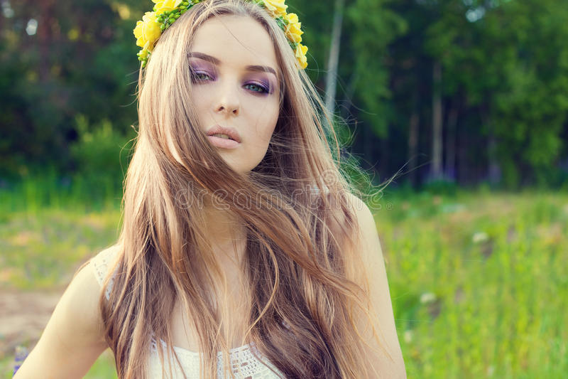 Mooi sexy zoet meisje met lang haar en een kroon van gele rozen op zijn hoofd op het gebied, de wind die haar haar blazen royalty-vrije stock foto