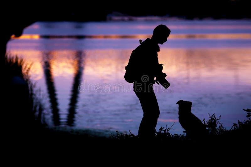 Mooi silhouet van een meisje dat met zijn hond communiceert stock foto