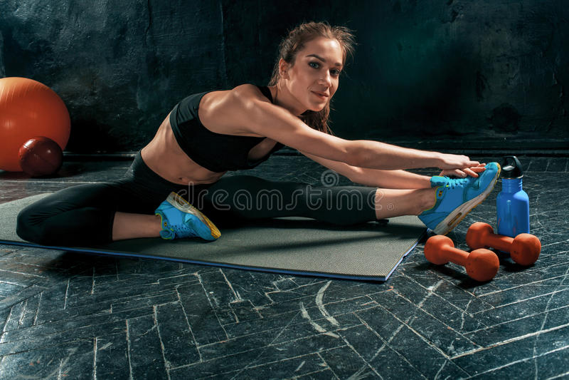 Mooi slank brunette die sommige uitrekkende oefeningen in een gymnastiek doen royalty-vrije stock foto