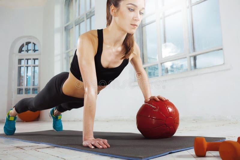 Mooi slank brunette die wat gymnastiek doen bij de gymnastiek stock afbeelding
