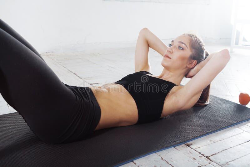 Mooi slank brunette doend wat duw UPS de gymnastiek royalty-vrije stock afbeeldingen