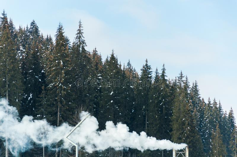 Mooi sneeuwbergbos in de dampen van de boilerinstallatie stock foto