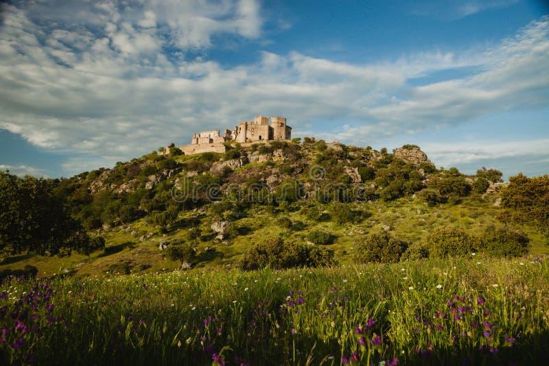 Mooi Spaans oud kasteel over een heuvel en een mooie hemel stock fotografie