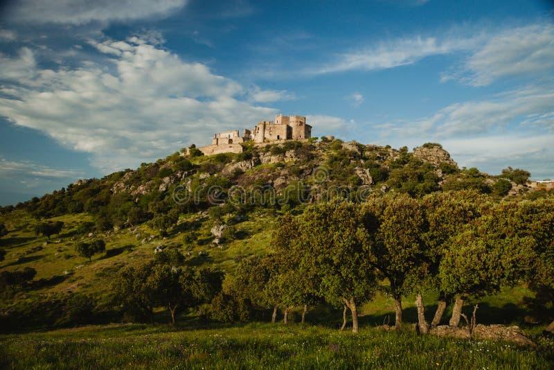 Mooi Spaans oud kasteel over een heuvel en een mooie hemel stock foto's