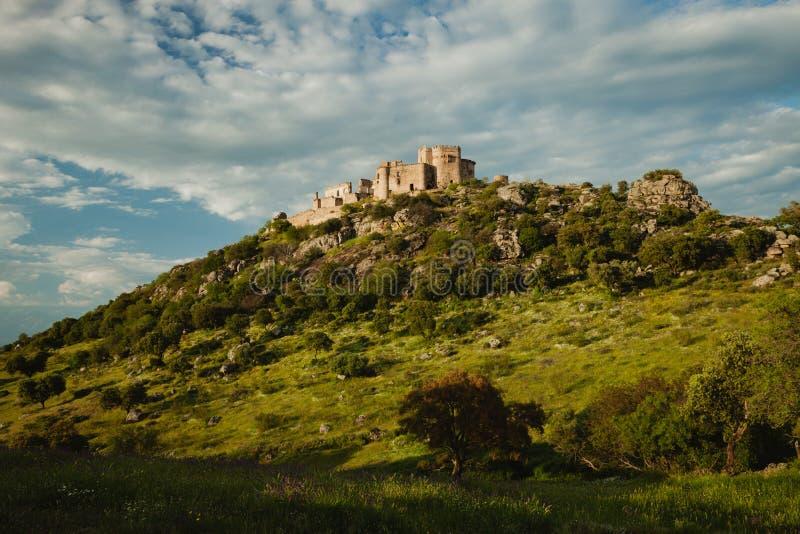 Mooi Spaans oud kasteel over een heuvel en een mooie hemel stock afbeelding