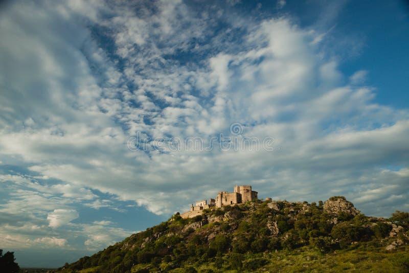 Mooi Spaans oud kasteel over een heuvel en een mooie hemel stock foto
