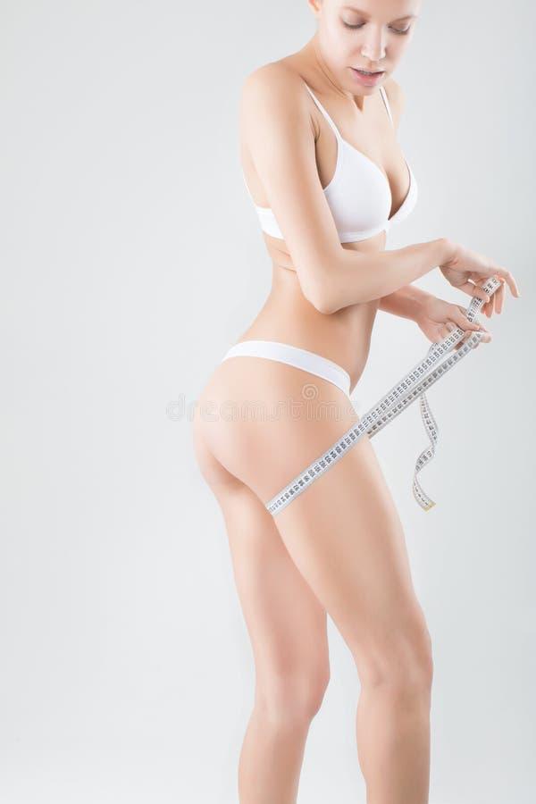Mooi sportief vrouwenlichaam met gele maatregel royalty-vrije stock afbeeldingen