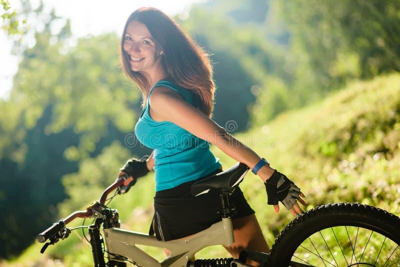 Mooi sportmeisje met fiets openlucht stock afbeelding