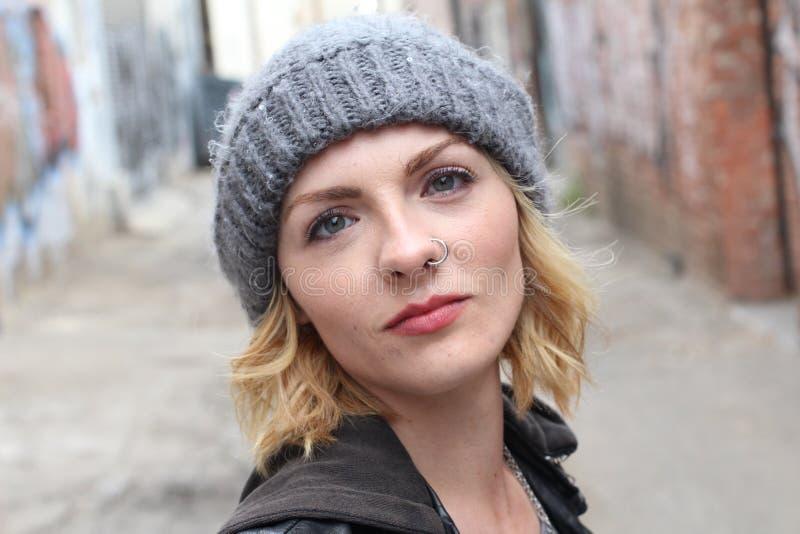 Mooi stedelijk meisje beanie en een populaire neusring die dragen stock fotografie