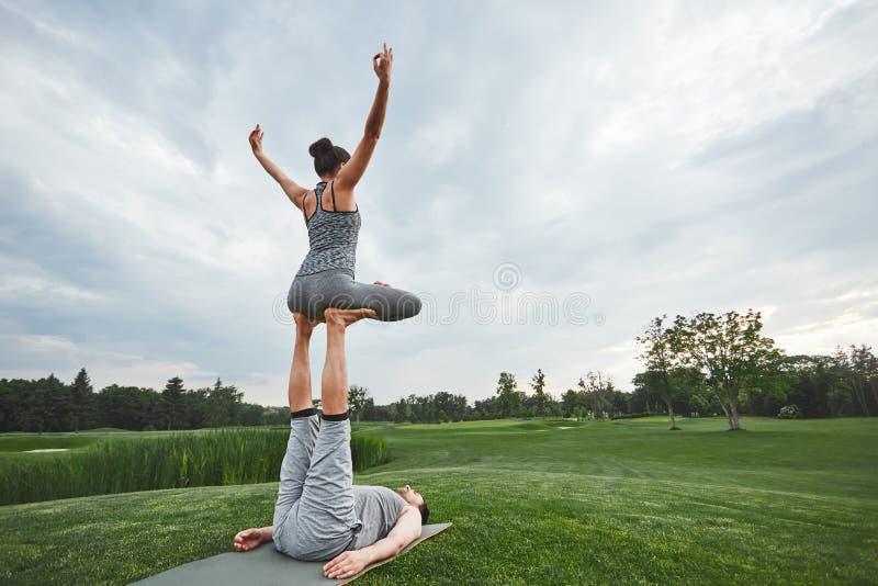 Mooi stelt met een partner De sterke man op een mat liggen en de in evenwicht brengende vrouw die in lotusbloem stellen op zijn v royalty-vrije stock fotografie
