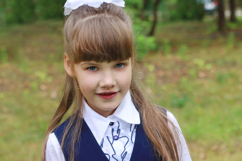Mooi stelt weinig schoolmeisje in eenvormig in groen park royalty-vrije stock afbeelding