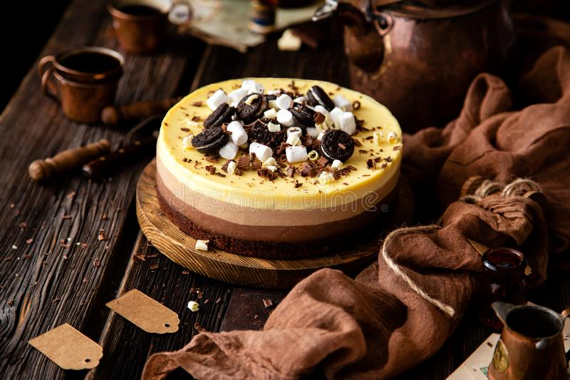 Mooi stilleven met eigengemaakte heerlijke drie chocoladekaastaart op houten tribune op rustieke lijst stock afbeelding