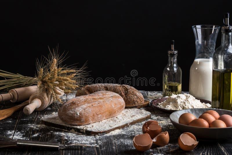 Mooi stilleven met verschillende soorten brood, korrel, bloem op gewicht, oren van tarwe, waterkruik melk en eieren stock foto's