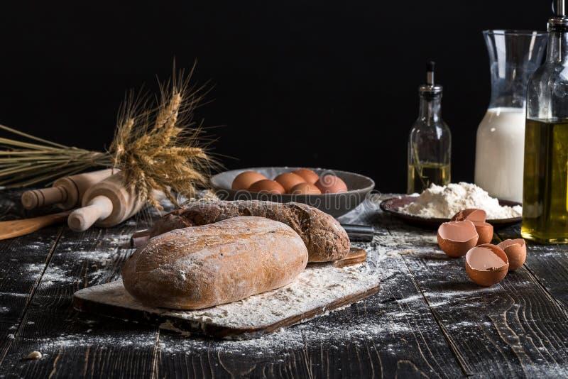Mooi stilleven met verschillende soorten brood, korrel, bloem op gewicht, oren van tarwe, waterkruik melk en eieren royalty-vrije stock foto