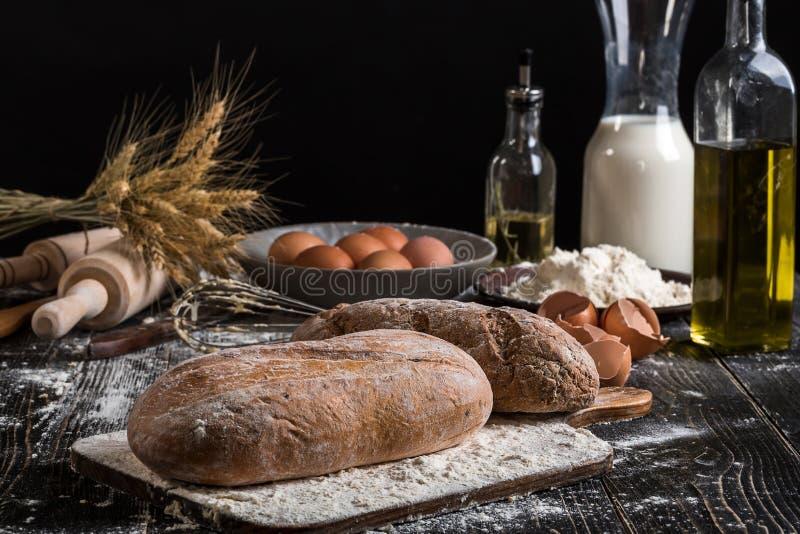 Mooi stilleven met verschillende soorten brood, korrel, bloem op gewicht, oren van tarwe, waterkruik melk en eieren stock afbeelding