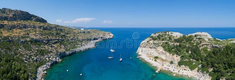 Mooi strandpanorama met boten op het eiland van Rhodos in Griekenland Turkoois water en blauwe hemel stock afbeelding